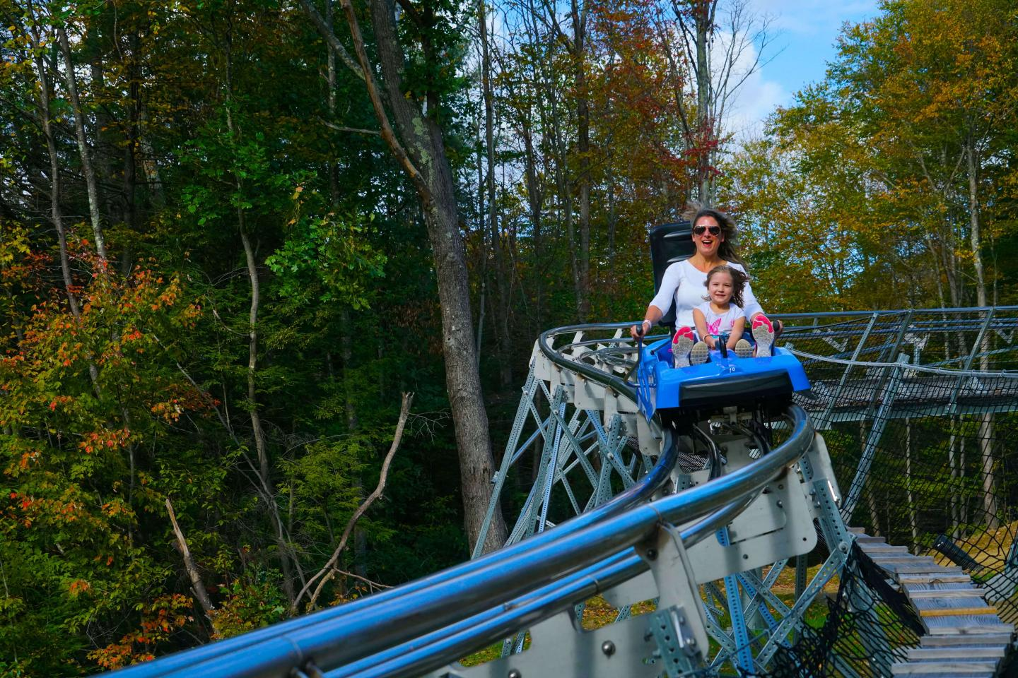 Mother and daughter riding Thunderbolt Mountain Coaster